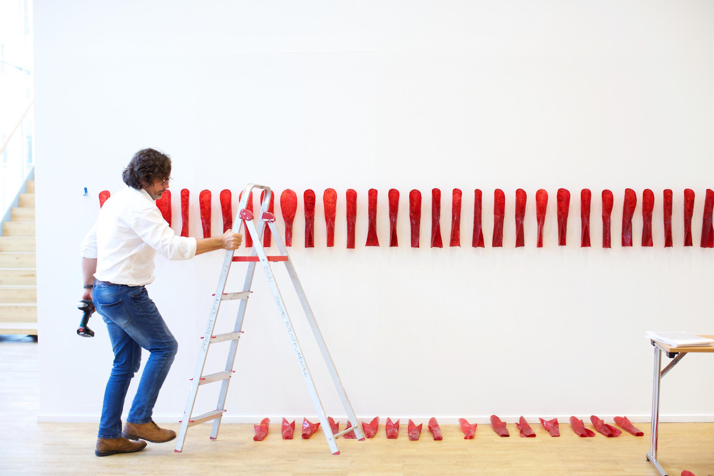 """Artist Marek Ranis helps install """"Red Curl"""" by Sonya Kellhier-Coombs."""